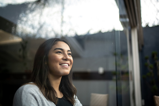 Happy young woman contemplating at home