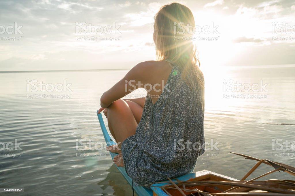 Junge Frau Betrachtung Sonnenuntergang sitzen auf Fischerboot, tropisches Klima – Foto