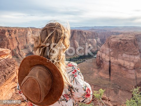 View of a girl looking at the famous horseshoe bend by the Colorado river at sunset, beautiful dramatic colourful sky. people travel concept
