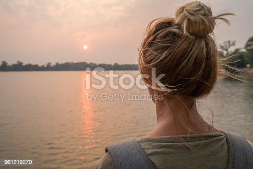 Young woman traveling in Cambodia visiting the temples of Angkor wat complex watching sunset from lakeshore. People travel discovery Asia concept. Shot at sunset, one woman only, adventure and exploration in Siem Reap, Southeast Asia.