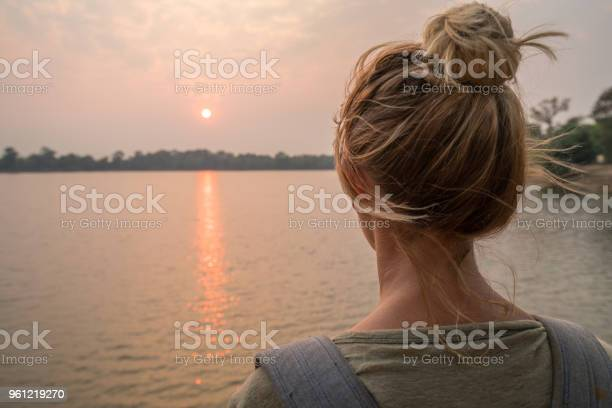 Photo of Young woman contemplating view at sunset from lakeside in Cambodia