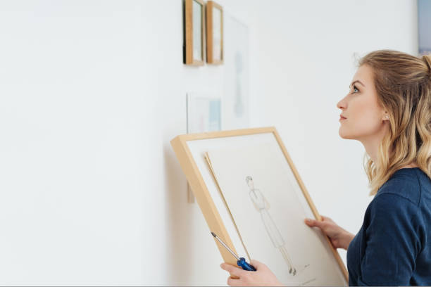 Young woman contemplating where to hang a picture stock photo