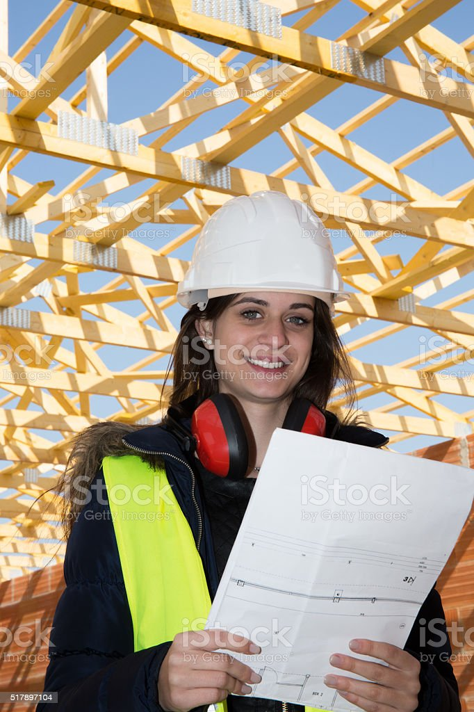 Young woman contractor looking at prints for her job stock photo