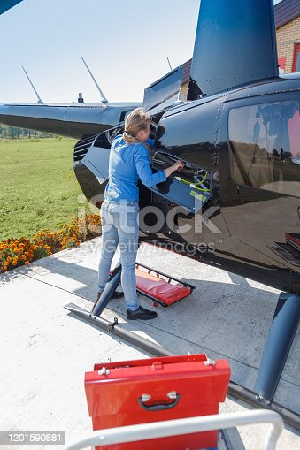 Young woman standing by the helicopter side opening and controlling hoses