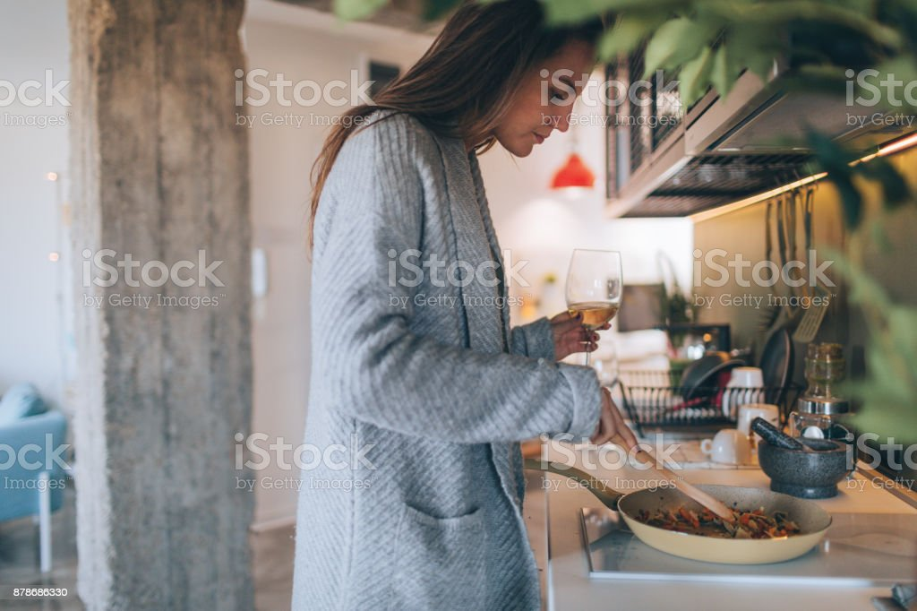 Young woman cooking and drinking wine stock photo