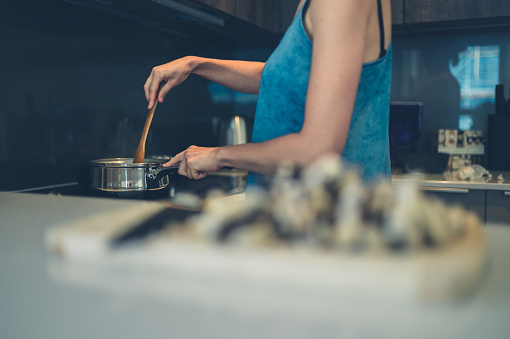 Young Woman Cooking In Kitchen Stock Photo - Download Image Now