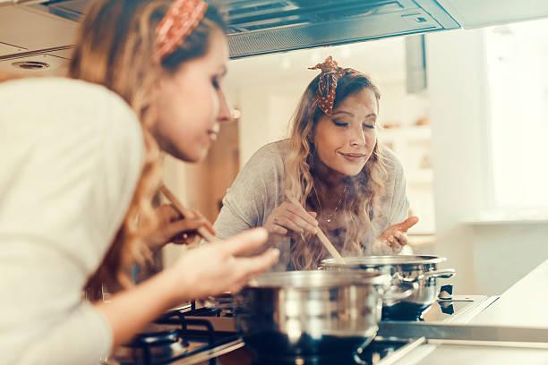 giovane donna cottura in cucina - annusare foto e immagini stock