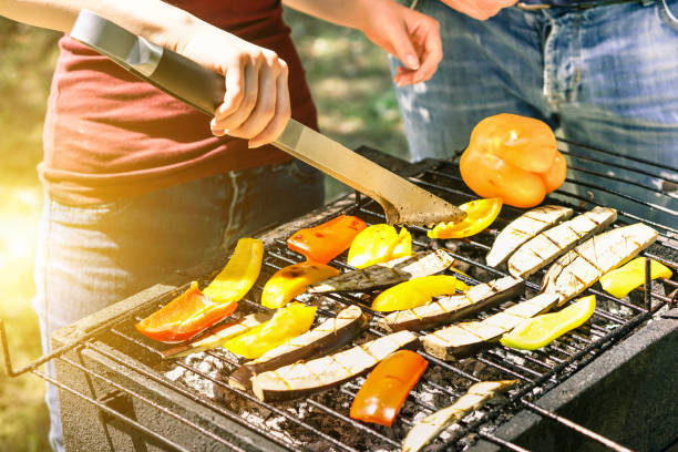 young woman cooking vegetables for vegetarian barbecue dinner outdoor - couple grilling peppers and aubergines for bbq - vegan and healthy lifestyle concept - soft focus on bottom barbecue tongs - grilled vegetables stock photos and pictures