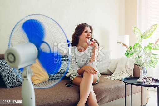 Young woman cooling down by electric ventilator at home while drinking water and hanging in phone. Summer heat.