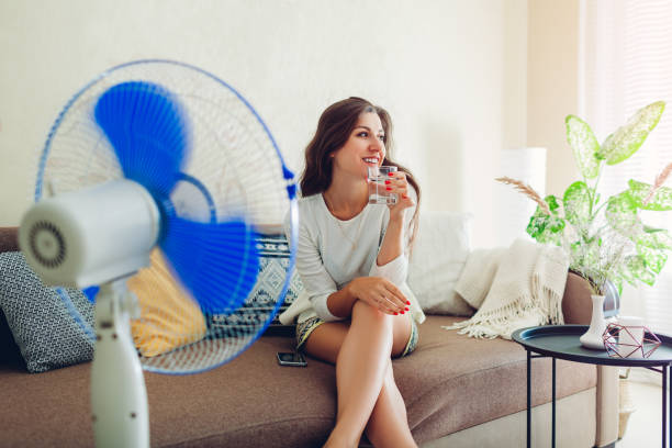 Young woman cooling down by ventilator at home while drinking water and hanging in phone. Summer heat.