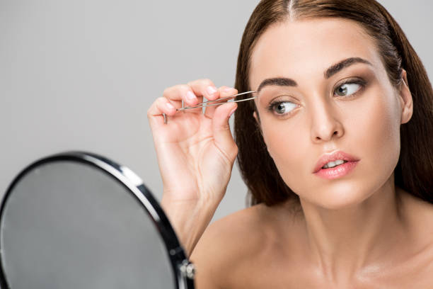 junge Frau, die Form der Augenbrauen korrigieren und Spiegel auf grau isoliert betrachten – Foto