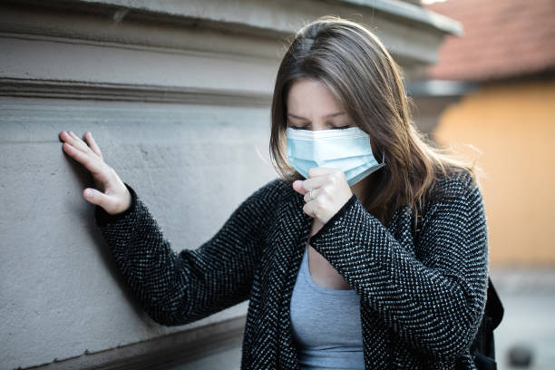 Young woman coughing under the mask stock photo