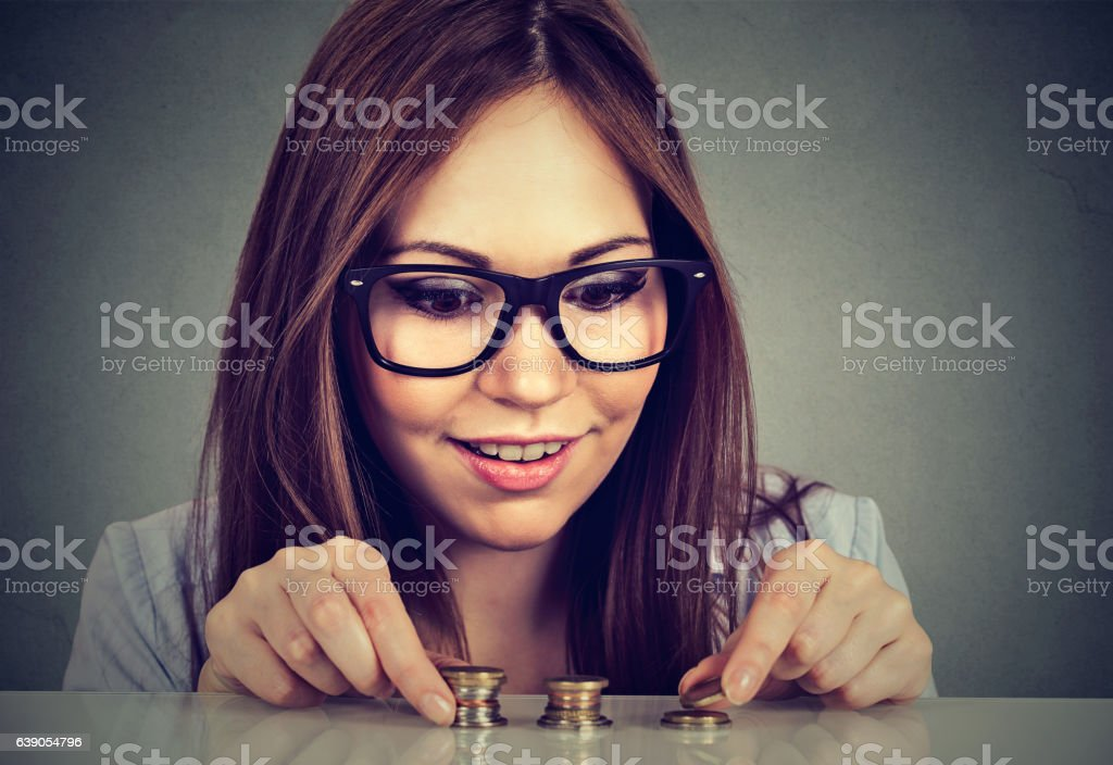 Young woman counting money stacking up coins stock photo
