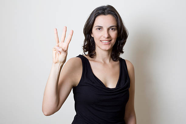 young woman counting number three - number 3 stock photos and pictures
