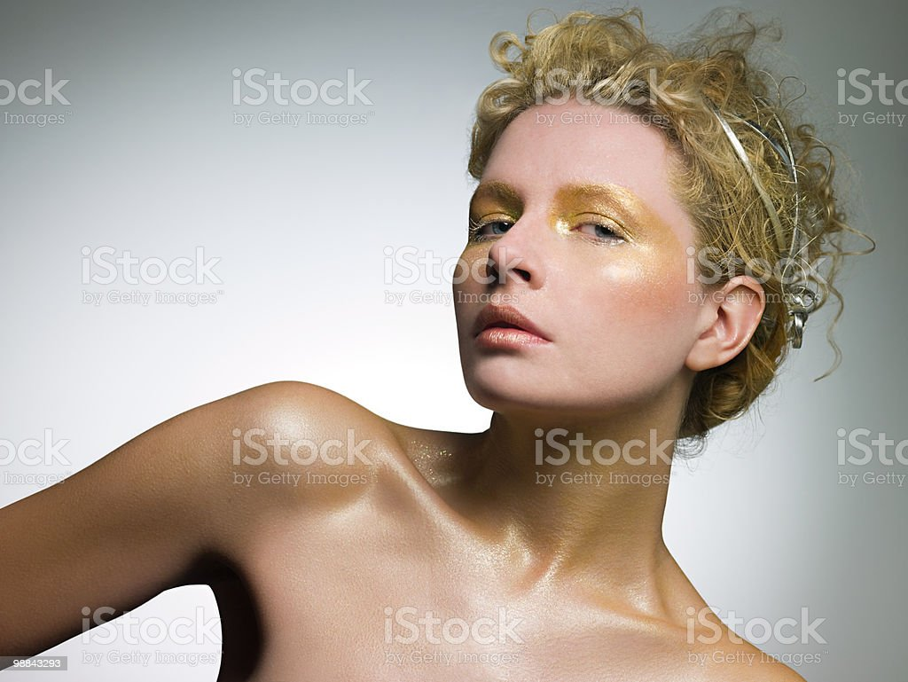 Young woman covered in gold make up royalty-free stock photo