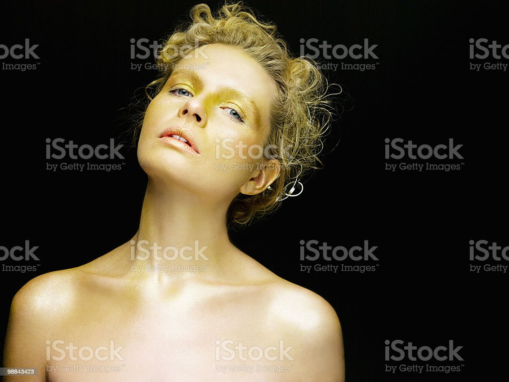 Young woman covered in gold make up royalty free stockfoto
