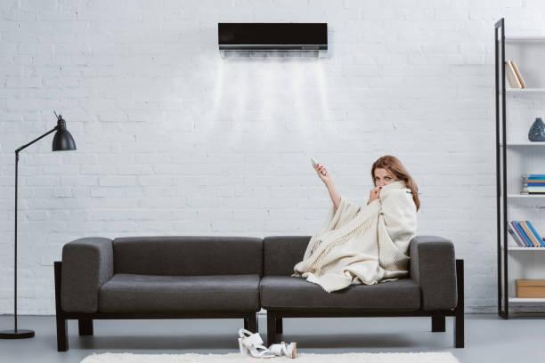 ung kvinna täckt med filt på soffan under luftkonditioneringen hängande på väggen och blåser kyls luften - kvinna ventilationssystem bildbanksfoton och bilder