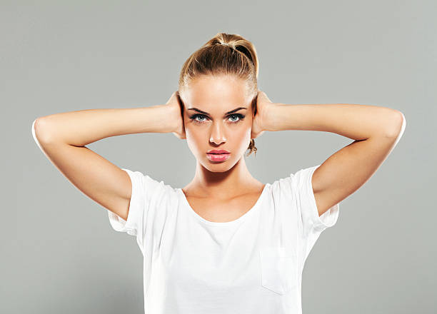 young woman covering ears with hands - covering ears stock photos and pictures