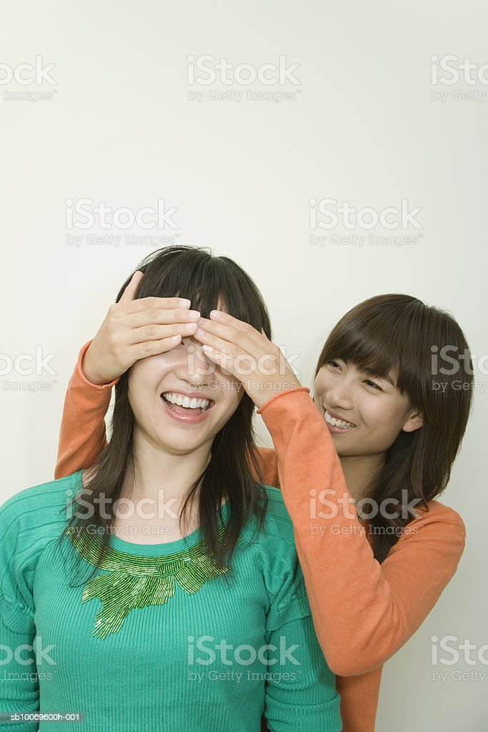 Young woman covering eyes of friend 免版稅 stock photo