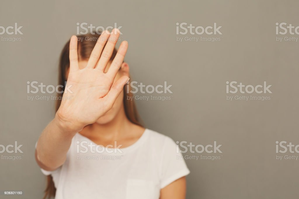 Young woman covering her face with palm stock photo