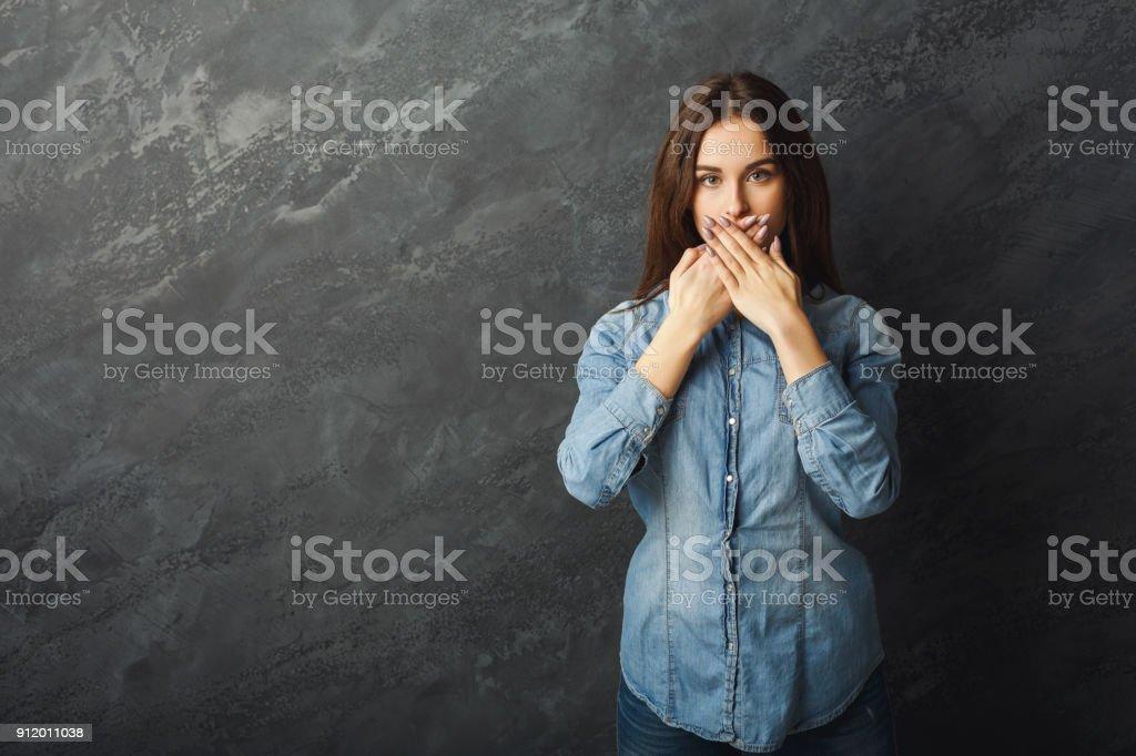 Mujer joven que cubre la boca con las manos - foto de stock
