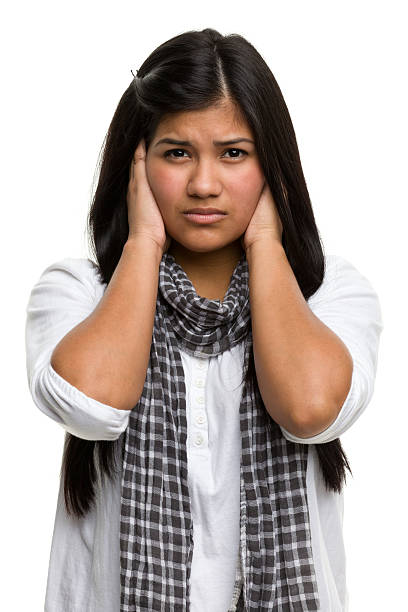 Young Woman Covers Ears Portrait of a young woman on a white background. hands covering ears hear no evil teenage girls women stock pictures, royalty-free photos & images