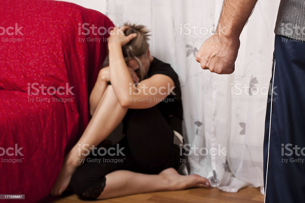 Young woman cowering in fear at the corner stock photo