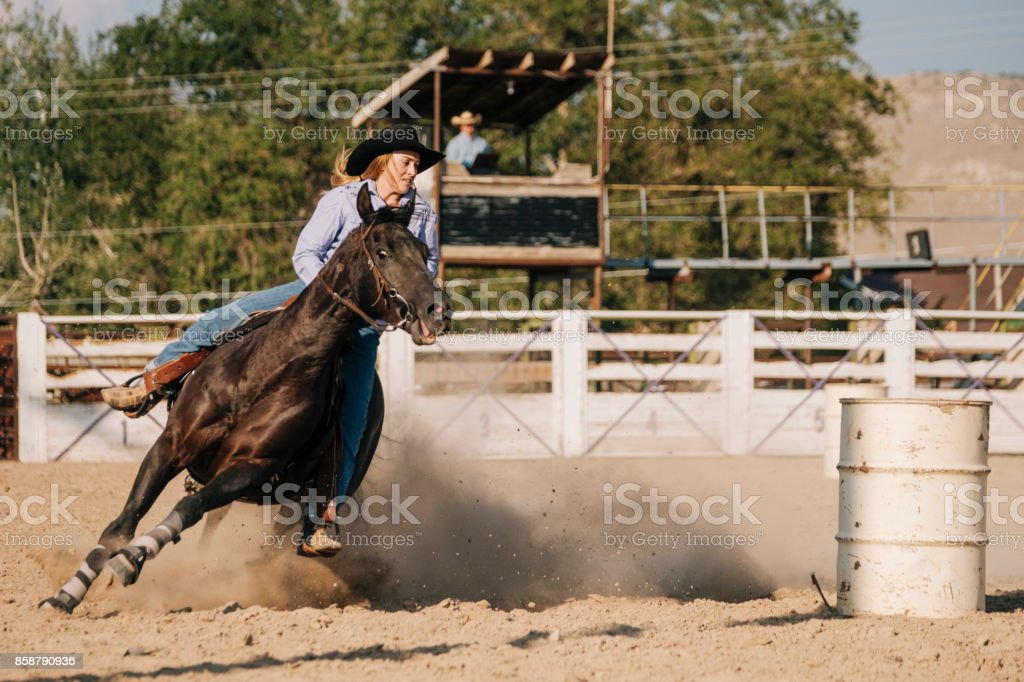 Young Woman Cowgirl Competing in Rodeo stock photo