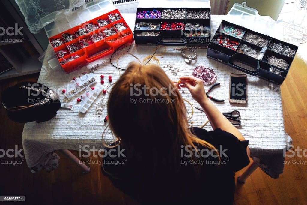Young woman crafting jewelry from scratch.