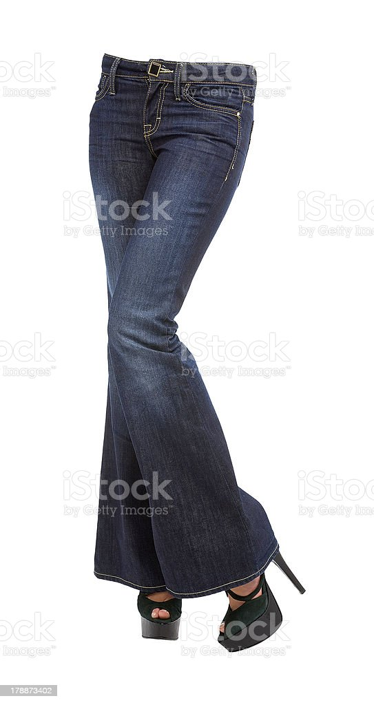 Young woman crossed legs in bell bottom jeans and stilettos stock photo