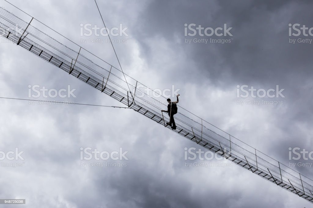 Young woman crosses a suspension bridge high up with dark clouds in background stock photo