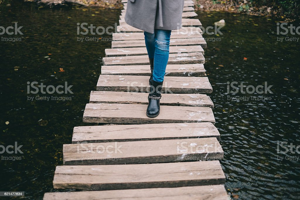 Young woman crossing a wooden bridge stock photo