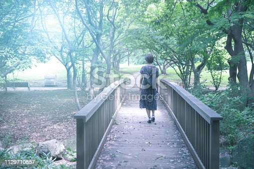 Young woman crossing wooden bridge in public park