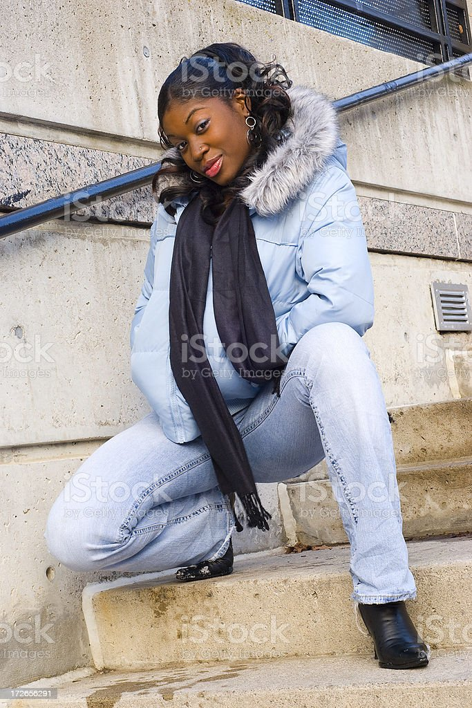 Young woman crouching on steps. royalty-free stock photo