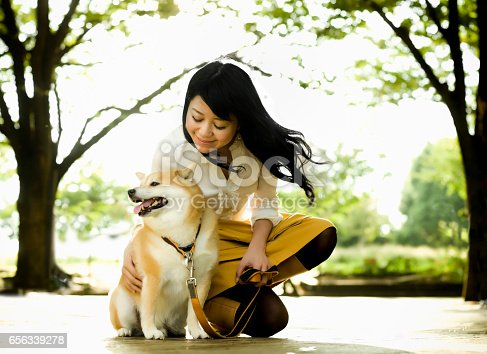istock Young Woman Crouching to Pet a Dog 656339278