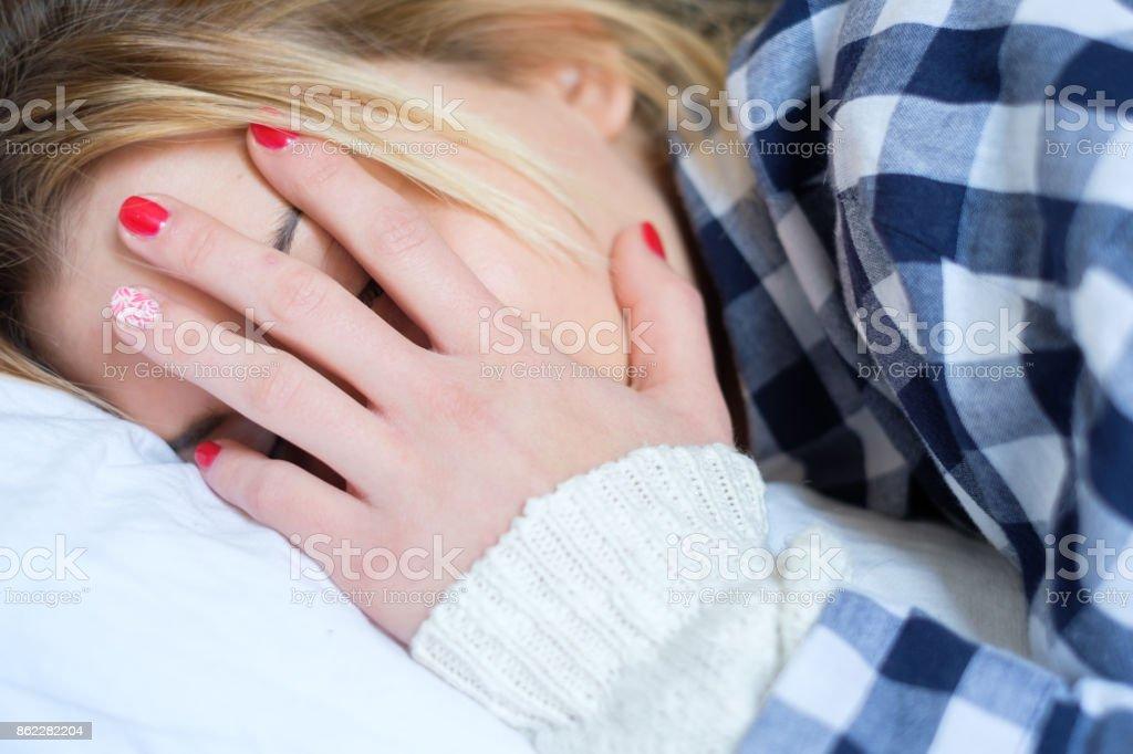 Joven mujer llorando en la cama después de la violencia doméstica en el hogar - foto de stock