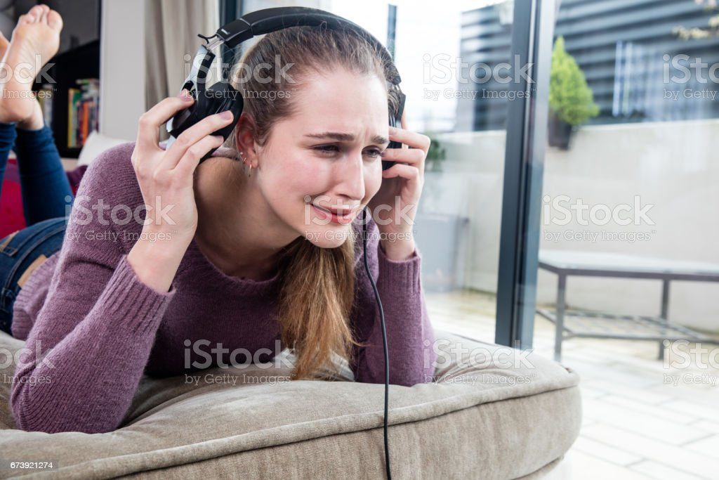 young woman crying in removing her headphones for noisy music stock photo