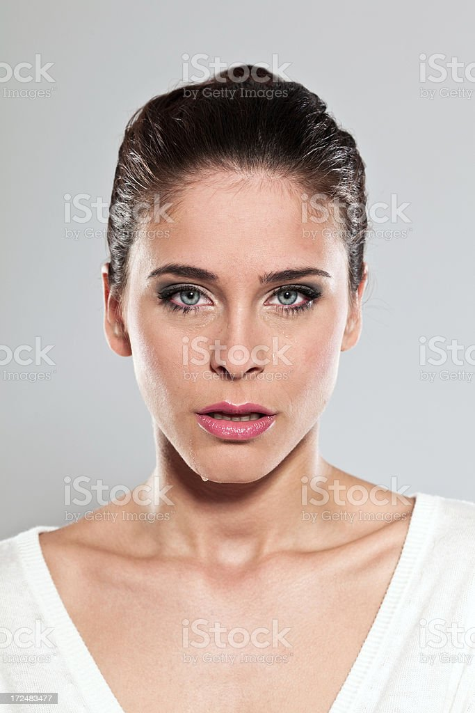 Young woman crying Portrait of a unhappy young woman looking at the camera and crying. Studio shot. 20-24 Years Stock Photo