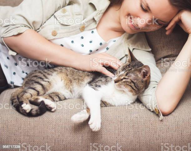Young woman cuddling cat at home picture id958717338?b=1&k=6&m=958717338&s=612x612&h=p6 bqm68rtr41mk0j3vd1eme5vfpysd eauz6sm09 o=