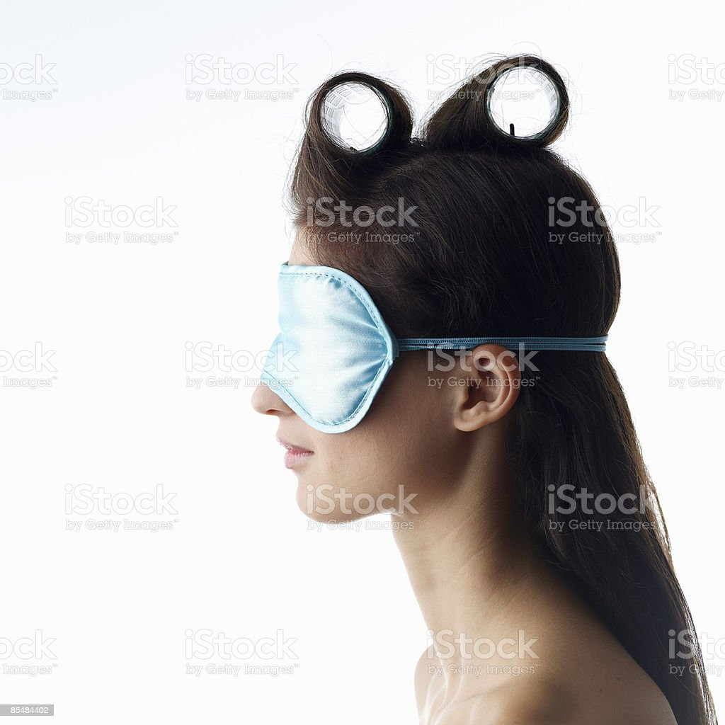 Young woman curling hair wearing eye shade royalty-free stock photo