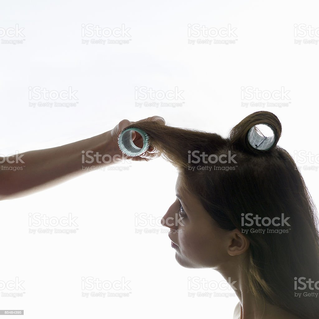 Young woman curling hair with hair roller, close-u royalty-free stock photo