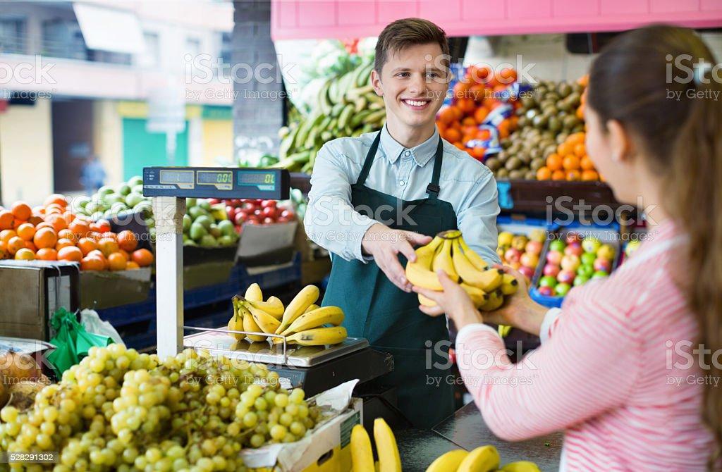 Young woman customer buying yellow bananas stock photo
