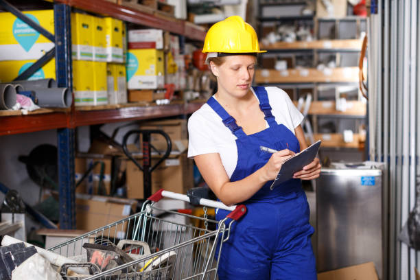 Young woman customer in helmet with  notebook looking construction  materials stock photo