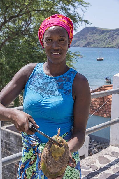 Young woman cutting a coconut, on the beach of Tarrafal - foto de stock