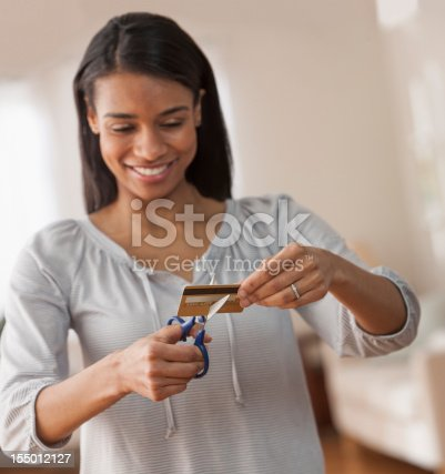 Young Woman African american Cutting up Credit Card Smiling after having gotten out of debt. squared composition