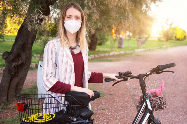 Young woman cycling and wearing protective mask stock photo