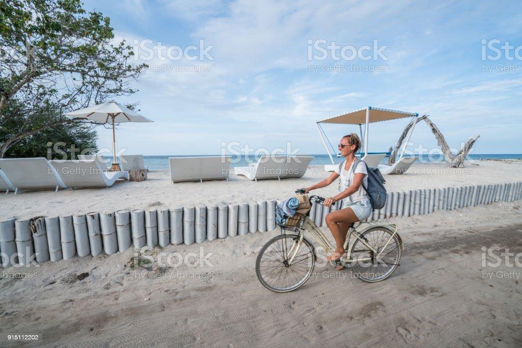 Junge Frau am Strand morgens Radfahren – Foto