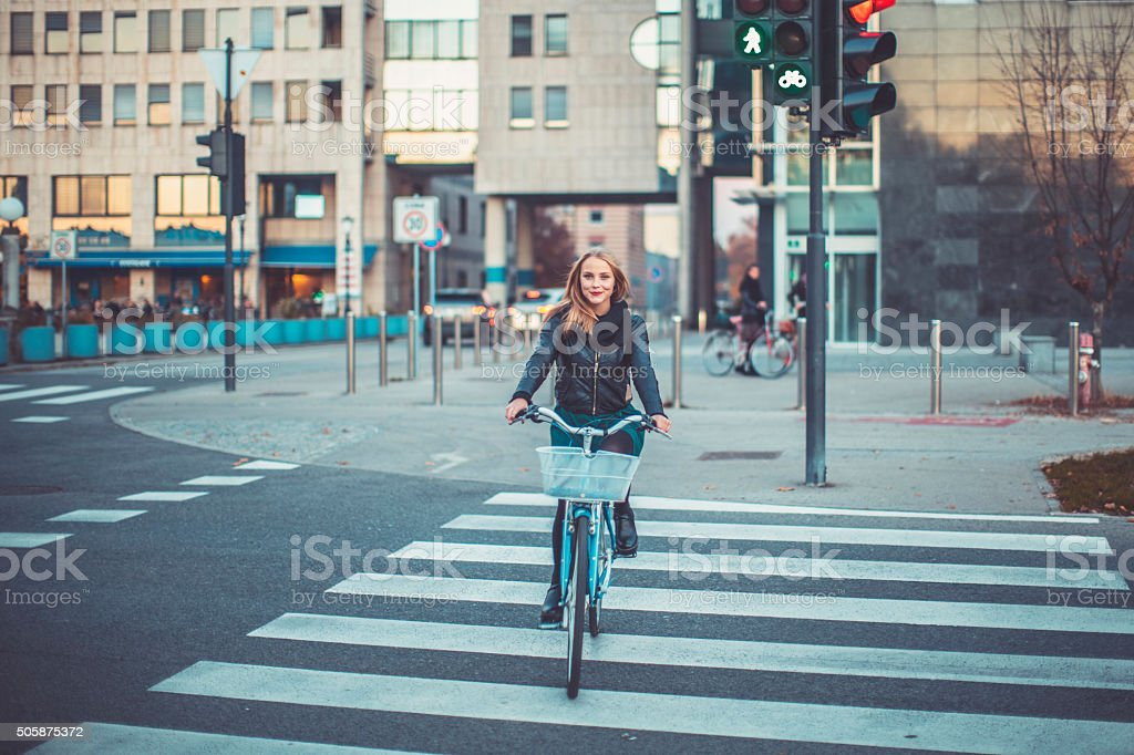 Young woman cycling, crossing the street stock photo