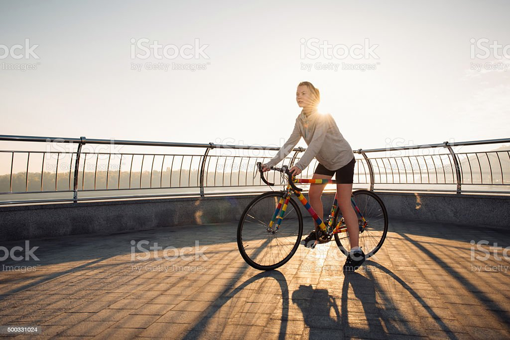 Young woman cycling in the morning city stock photo