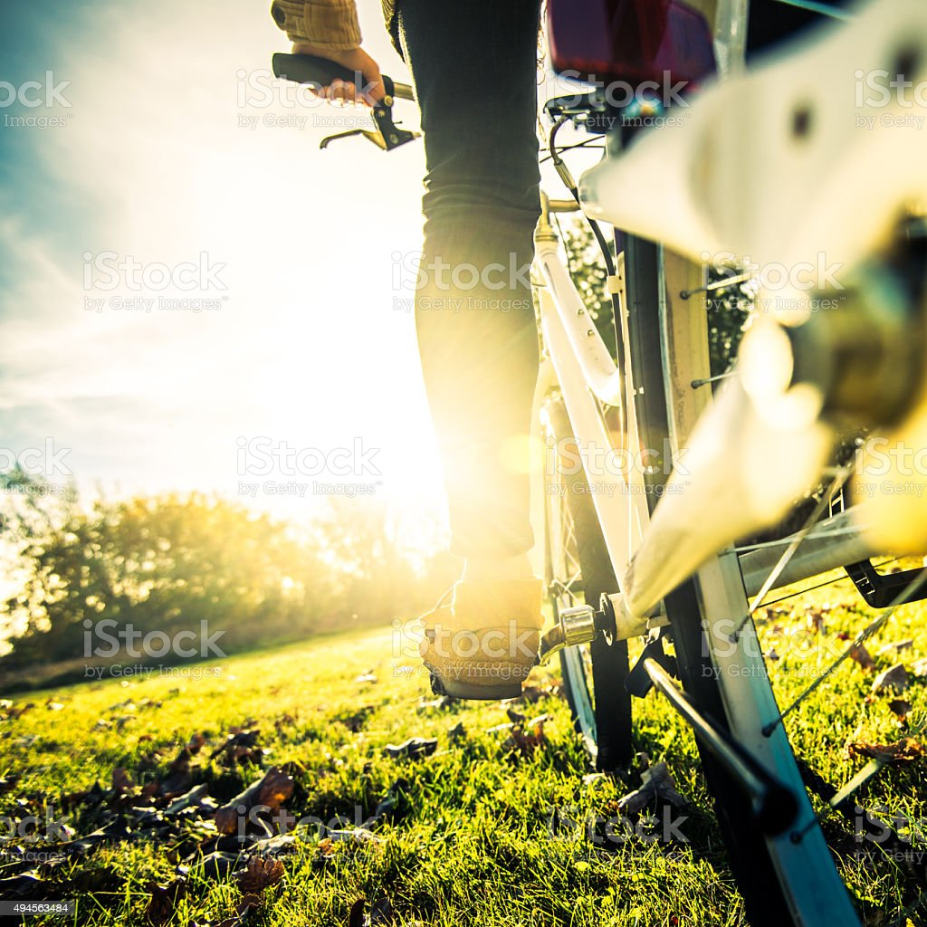 Young woman cycling in the park at sunse stock photo